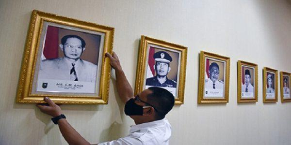 Seorang pegawai merapikan letak foto Gubernur Riau pertama, Sultan Mohammad (SM) Amin Nasution yang dianugerahi gelar Pahlawan Nasional, di Kantor Gubernur Riau, Pekanbaru, Senin (09/11/2020). (Foto: kominfo.go.id / antarafoto)