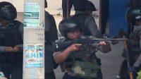 Polisi mengarahkan senjatanya saat pasukan keamanan melakukan tindakan keras terhadap pengunjuk rasa kudeta militer di Myitkyina di negara bagian Kachin Myanmar [Foto: Al Jazeera/Screengrab/Myitkyina News via AFPTV]