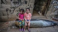 Dua bocah Palestina kakak beradik duduk di atas rudal yang tidak meledak. Rudal ditembakkan pesawat tempur Israel di Gaza (Foto: BBC/EPA)