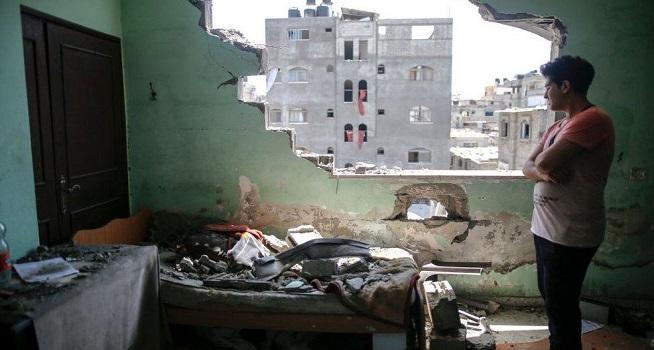 Seorang pemuda Gaza mengamati kondisi rumahnya yang hancur akibat serangan Israel (Dok. BBC/Getty Images)