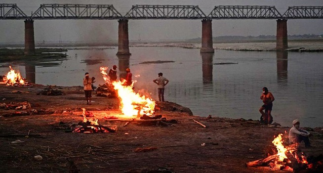 Tumpukan kayu dengan api berkobar menyala di Sungai Gangga di Allahabad, tempat mayat-mayat mengapung selama berhari-hari (Dok. BBC/Getty Images)